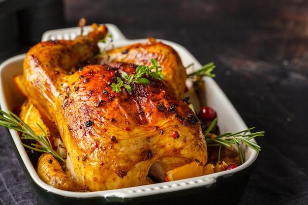 Poulet cuit au four avec des épices, des canneberges, des oranges et des oignons dans un plat en verre.