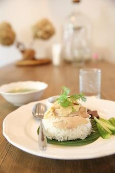 Poulet cuit à la vapeur gastronomique de cuisine thaïlandaise avec du riz, khao mun kai sur fond de bois