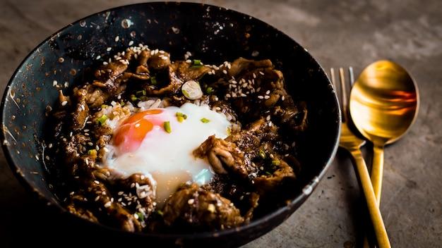 Poulet avec du riz, des oignons et du brocoli sur la table. vue horizontale d'en haut. le riz japonais sert avec du poulet dans une sauce teriyaki et des œufs