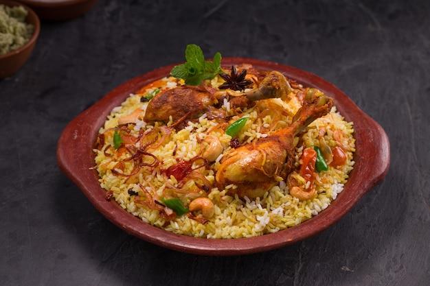 Poulet dum biriyani utilisant du riz jeera et des épices disposés dans de la terre cuite