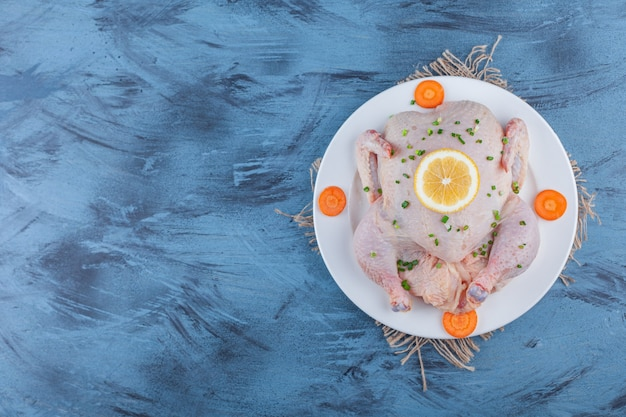 Poulet entier, citron et carottes tranchées sur une assiette sur une toile de jute, sur le fond bleu.