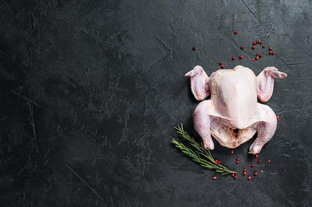 Poulet entier cru au romarin et au poivre rose. vue de dessus.