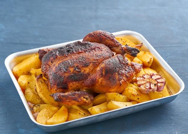 Poulet entier cuit au four dans une casserole bleue sur une table bleu foncé, viande rôtie avec des pommes de terre. vue de côté