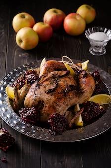 Poulet entier cuit au four avec des herbes, servi avec des tranches de grenade et de citron sur un plat en métal.