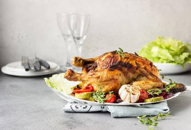 Poulet entier cuit au four avec légumes, thym et salade sur une plaque en céramique blanche.
