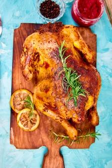 Poulet entier cuit au four avec des sauces sur une planche en bois sur fond bleu.