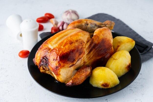 Poulet entier grillé dans une assiette noire sur une table blanche, viande cuite au four avec pommes de terre. vue de côté