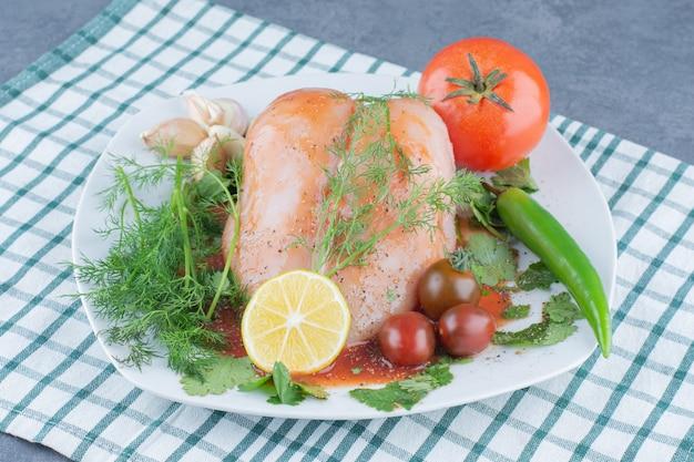 Poulet entier mariné sur assiette avec légumes.