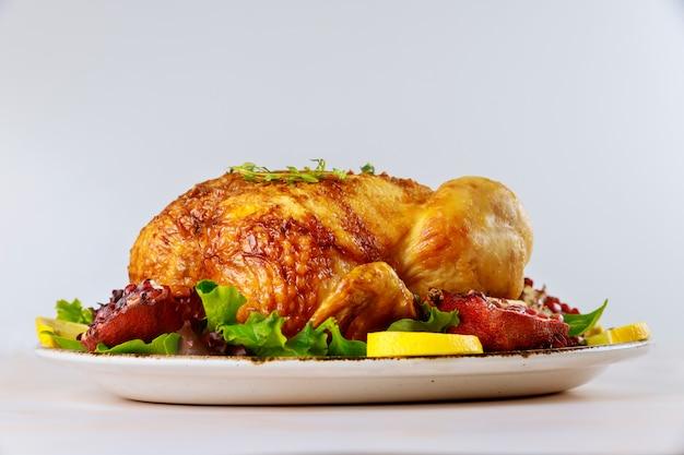 Poulet entier rôti sur une assiette avec salade et grenade