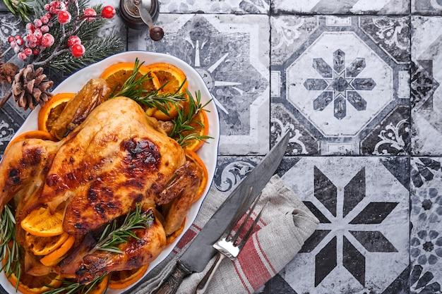Poulet entier rôti ou cuit au four au romarin et aux oranges, fait maison pour un dîner en famille sur une table en pierre brune. vue de dessus avec espace de copie.