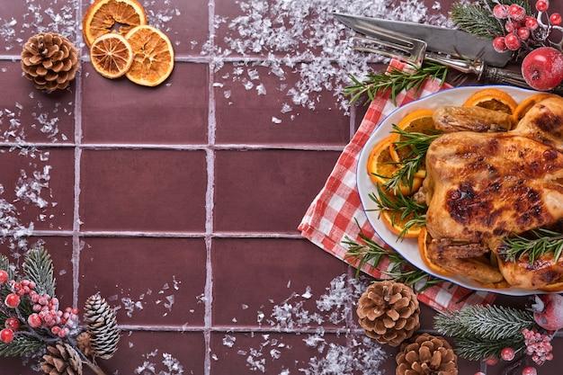 Poulet entier rôti ou cuit au four avec du romarin et des oranges, fait maison pour le dîner familial traditionnel de noël sur une table en pierre brune. vue de dessus avec espace de copie.