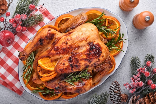 Poulet entier rôti ou cuit au four avec du romarin et des oranges, fait maison pour le dîner familial traditionnel de noël sur une table rustique gris pierre. vue de dessus avec espace de copie.