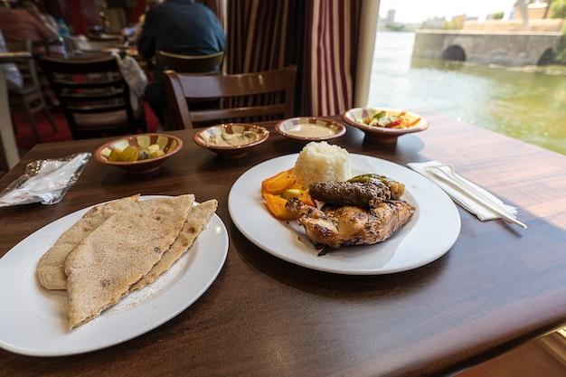 Poulet épicé chaud tikka masala dans un bol. poulet au curry avec riz, pain naan indien au beurre, épices, herbes. pain plat de pain patta, une cuisine traditionnelle d'israël, d'egypte, de jordanie, du moyen-orient.