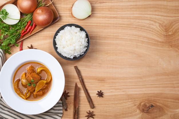 Poulet épicé et riz sur fond de bois