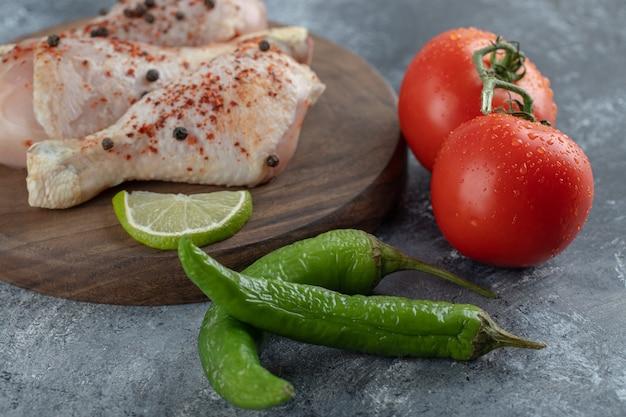 Poulet frais cru sur planche à découper avec des légumes frais.