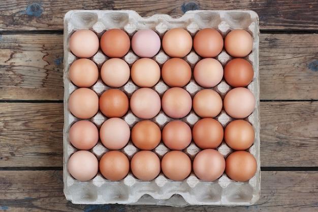 Poulet frais, oeufs bruns dans l'emballage sur un plancher en bois, la vue de dessus.