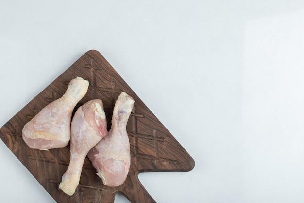 Poulet frais sur planche à découper en bois sur fond blanc.