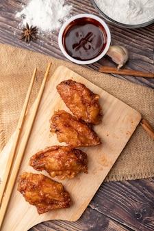 Poulet frit au barbecue coréen chaud et épicé sur une planche à découper en bois