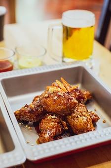 Le poulet frit coréen golden crunchy (base huraideu-chikin) se mélange avec la sauce épicée, le chili et l'ail.