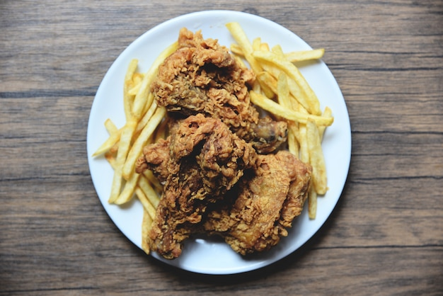 Poulet frit croustillant sur une plaque blanche avec des frites sur la table à manger