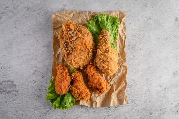 Poulet frit croustillant saupoudré de graines de poivre avec de la salade sur un papier brun.