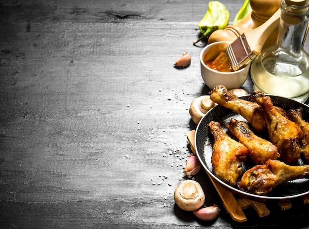 Poulet frit dans une poêle avec champignons, ail et sauce tomate.