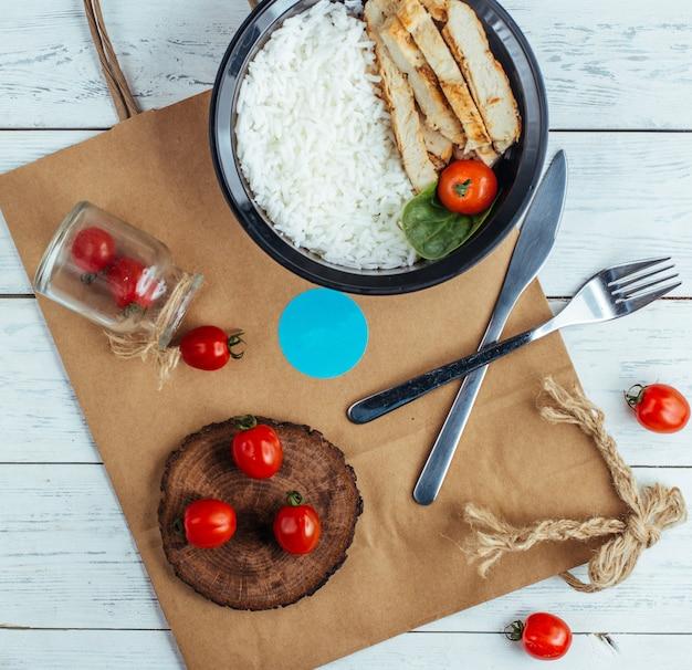 Poulet frit avec du riz et des tomates sur une planche de bois