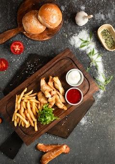 Poulet frit et frites sur une planche de bois