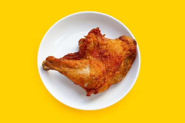 Poulet frit en plaque blanche sur fond jaune.