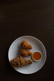 Poulet frit et sauce sur une assiette blanche