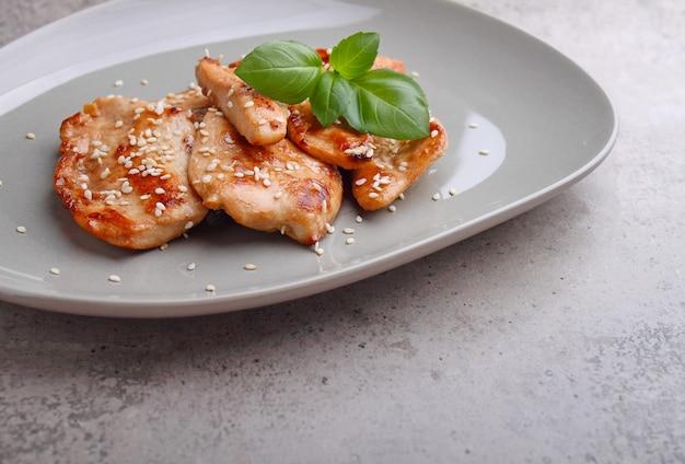 Poulet frit à la sauce soja sur une assiette décorée de graines de sésame et de basilic, copy space