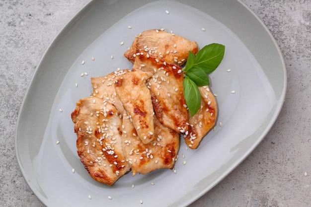 Poulet frit à la sauce soja sur une assiette décorée de graines de sésame et de basilic, vue du dessus