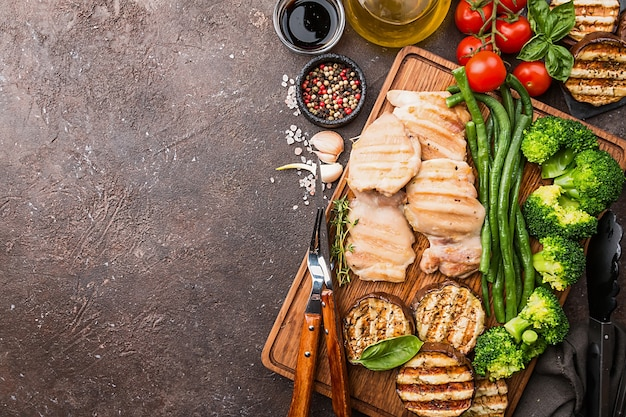 Poulet grillé des aliments sains avec des légumes sur une planche à découper sur une surface sombre, vue du dessus