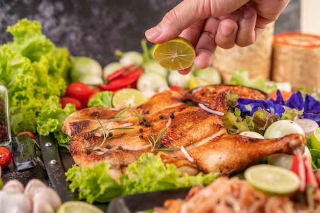 Poulet grillé sur l'assiette avec du piment à l'ail et saupoudré de graines de poivre.