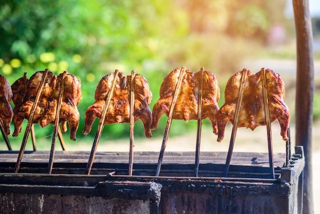 Poulet grillé sur une grille en bois et grill
