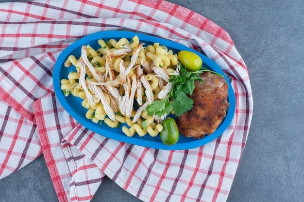 Poulet grillé et pâtes sur plaque bleue.