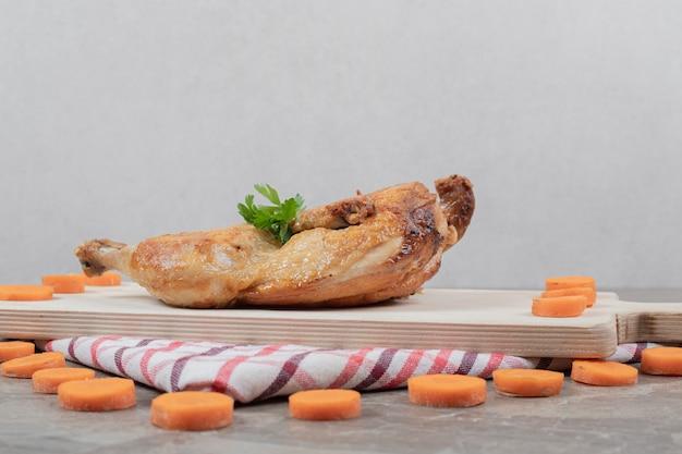 Poulet grillé sur planche de bois avec des tranches de carottes. photo de haute qualité