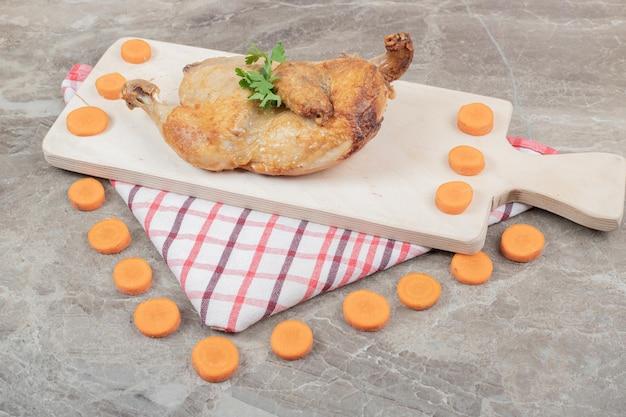 Poulet grillé sur planche de bois avec des tranches de carottes.