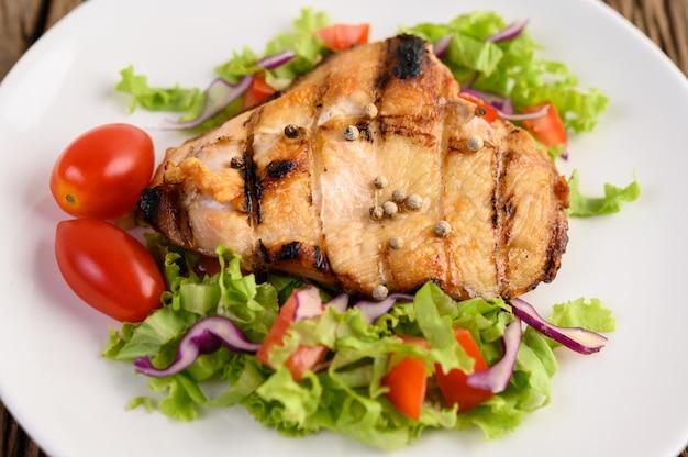 Poulet grillé sur une plaque blanche avec une salade de tomates, carottes et piments coupés en morceaux.