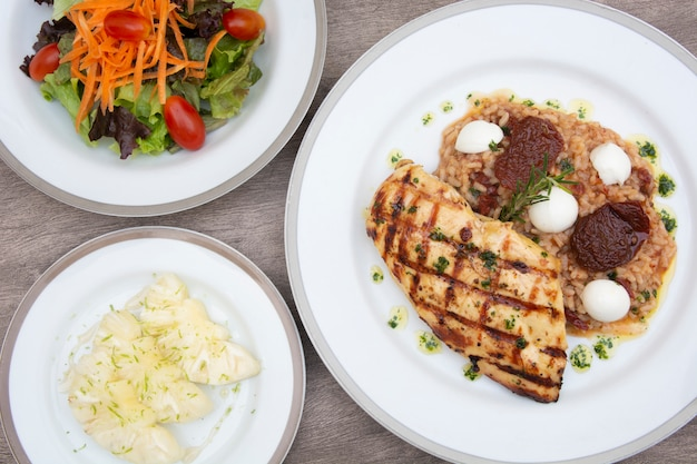 Poulet grillé, riz au fromage et aux tomates, carotte, letucce et ananas en tranches sur la vaisselle sur une table en bois