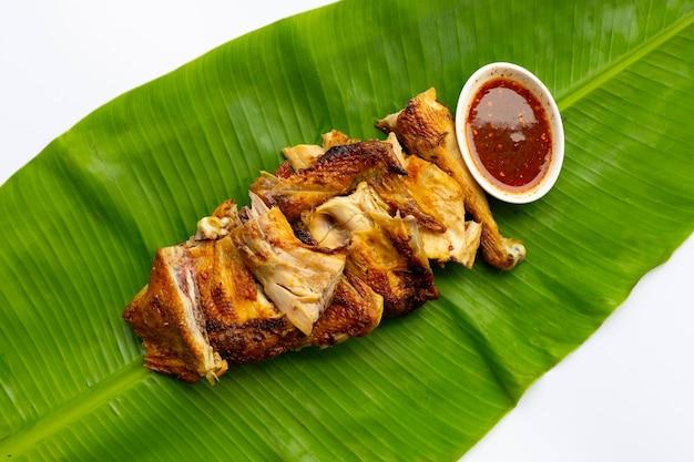 Poulet grillé avec sauce épicée, cuisine de style thaïlandais sur feuille de bananier sur une surface blanche