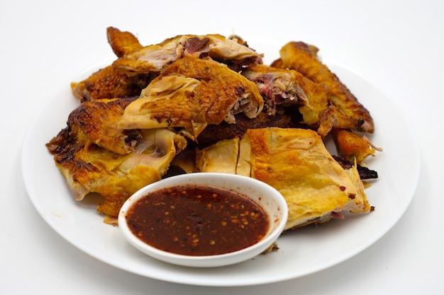 Poulet grillé avec sauce épicée sur surface blanche