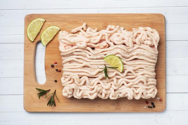 Poulet haché sur une planche à découper avec des épices et de la lime. espace de copie de tableau blanc.