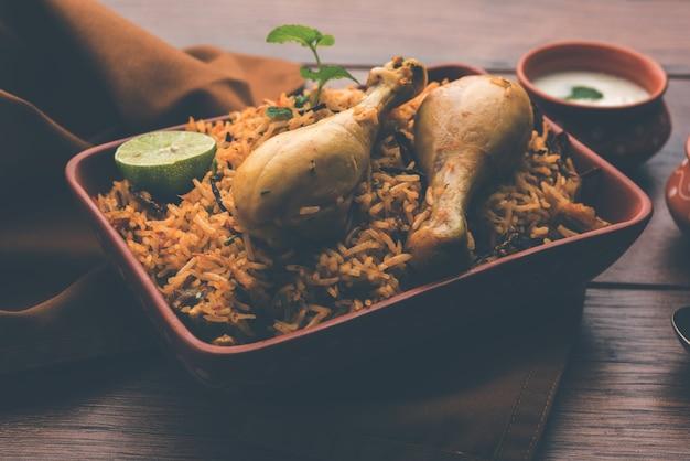 Poulet indien biryani servi dans un bol en terre cuite avec du yaourt sur fond blanc. mise au point sélective