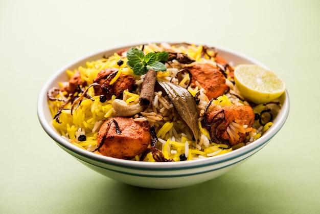 Poulet indien tikka biriyani servi dans un bol avec du yaourt. mise au point sélective
