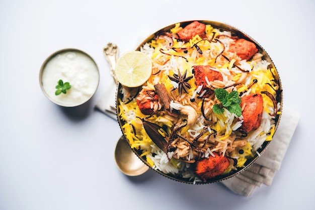Poulet indien tikka biriyani servi dans un bol avec du yaourt