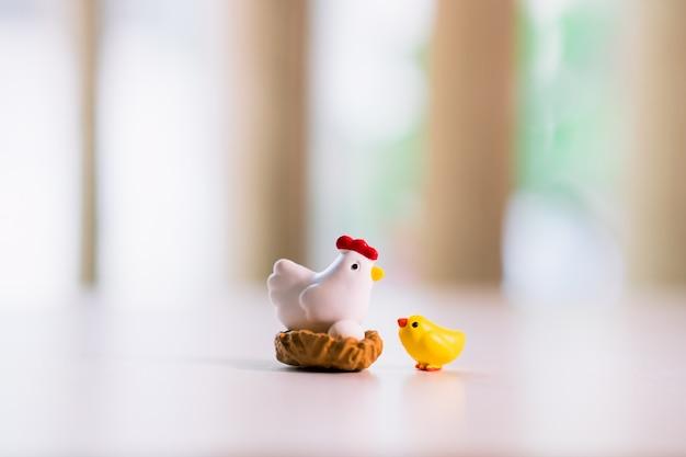 Poulet jaune et poule debout sur le nid