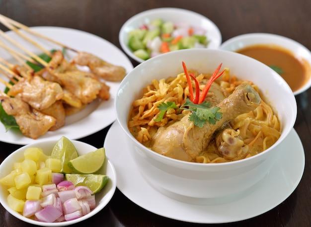 Poulet khao soi, plat de nouilles du nord de la thaïlande avec poulet et soupe au curry de noix de coco, illustré avec des nouilles croustillantes et d'autres légumes