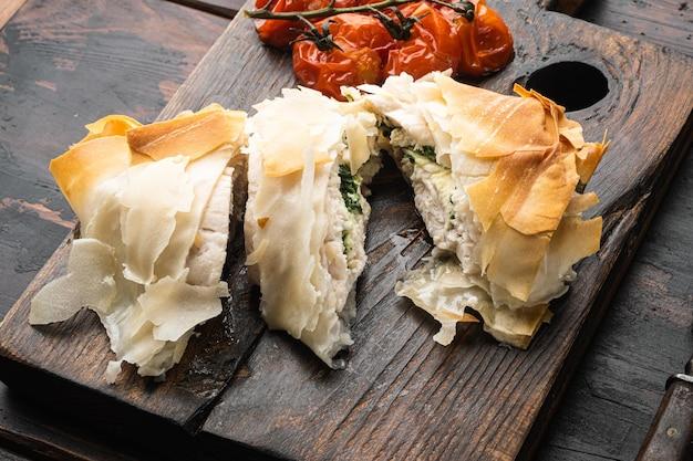 Poulet kiev à l'ail sauvage, avec des tomates cerises au four, sur une planche de service, sur un vieux fond de table en bois foncé