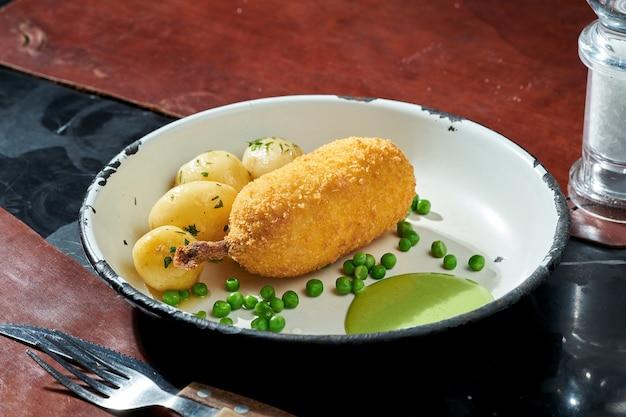 Poulet kiev aux petits pois, pommes de terre et sauce verte dans une assiette blanche sur une surface sombre. lumière forte. escalope frite